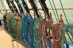 Ship multi-colored ropes on the rails amd wooden deck. royalty free stock images