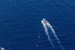 Ship navigates into beautiful blue water near Santorini island,. Aegean sea in Greece Royalty Free Stock Photos