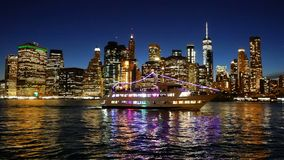 Ship navigating Hudson River Cityscape of Lower Manhattan New York City at night stock video