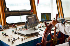 Ship navigation. Close view into captain's cabines, navigation equipment and captain's hand on rudder during cruising Royalty Free Stock Photography