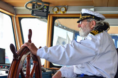 Ship navigation. Experienced captain, old sea dog with grey hair and beard on his working place,  cabine Royalty Free Stock Photo