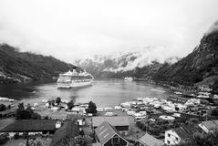 Ship in norwegian fjord on cloudy sky. Ocean liner in village harbor. Travel destination, tourism. Adventure, discovery. Geiranger, Norway - January 25, 2010 royalty free stock photography