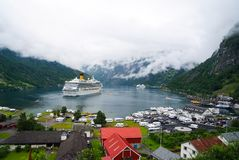 Ship in norwegian fjord on cloudy sky. Ocean liner in village harbor. Travel destination, tourism. Adventure, discovery. Geiranger, Norway - January 25, 2010 stock photo