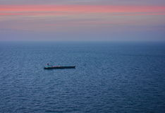 Ship on the ocean at dusk Royalty Free Stock Photography