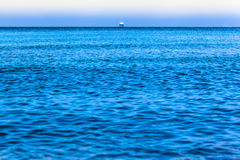 Ship at the Ocean Horizon. Wide view over the blue ocean water toward a vessel straight away at the horizon royalty free stock images
