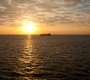 Ship on ocean at sunset Royalty Free Stock Image