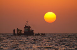 Ship and orange sun Stock Image