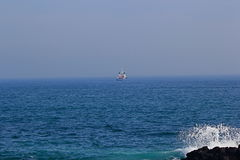 A ship out at sea. With foreground of waves crashing on volcanic rock Royalty Free Stock Image