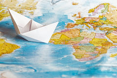 Ship from a paper on the geographical map stock images
