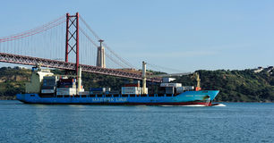 A ship pass under The 25th of April Bridge, Lisbon, Portugal Royalty Free Stock Images