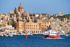 The ship  passes the bay along the Birgu coast, Malta. The view of historical buildings of Birgu across the Dockyard creek  with Cruises ship passing along the Stock Image