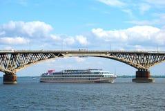 A ship passes under the bridge. Through the Volga River in Saratov Stock Photos