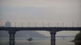 A ship passes under the bridge on the river stock footage