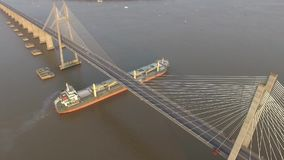 Ship passing under a bridge. Aerial view of ship passing under a bridge. A summer afternoon in Rosario, Santa Fe, Argentina stock footage