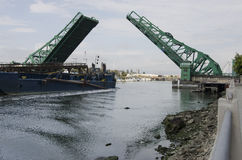 Ship Passing Under a Raised Green Drawbridge Stock Image