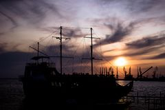 A large, old ship stands at the dock at sunset. bright beautiful sky. Ship and port at night.A large, old ship stands at the dock at sunset. bright beautiful sky stock images