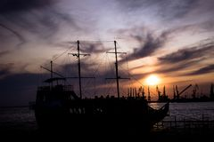 Silhouette of a large, old ship at the dock at sunset. bright beautiful sky. Ship and port at night.Silhouette of a large, old ship at the dock at sunset. bright stock photo