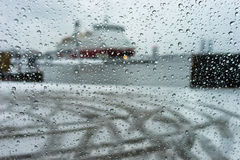 Ship in the port through the raindrops on glass in a strong snow Stock Photo