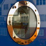 Ship porthole. With quayside reflections and salt spray marks Stock Image