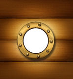 Ship Porthole Window. Porthole or ship window on an old wood frame wall as a nautical and marine symbol of a cruise sailboat or boat passenger cabin window made Royalty Free Stock Photo