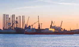 Ship-repair industry and ship. Ship-repair industry at sunset with ship passing by on the river Royalty Free Stock Photo