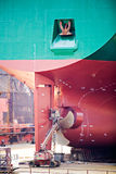 Ship repairs in dry dock. Rear view with screw propeller maintenance Stock Image