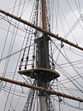 Ship Rigging. Mast and rigging on an old wooden ship against a grey, foreboding sky Stock Image