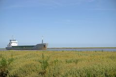 Ship in river. Cargo vessel Scot Ranger travelling up the river Great Ouse on it`s way to Kings Lynn, viewed from across the saltmarsh. This vessel has Stock Photography