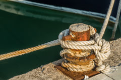 Ship rope bound to the quay. Ship rope tightly bound to the rusty quay Royalty Free Stock Photos