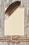 Ship rope, feather, spiral notebook and wood background Royalty Free Stock Photography