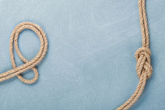 Ship rope knot on wooden texture background Royalty Free Stock Photography