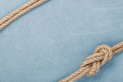 Ship rope knot on wooden texture background Stock Image