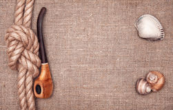 Ship rope, seashells and tobacco pipe. On hessian Royalty Free Stock Photos