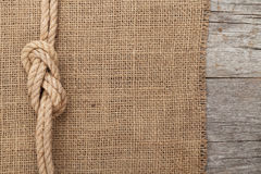 Ship rope on wood and burlap texture background Stock Images