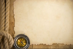 Ship ropes and compass on old paper. Parchment background at woood Royalty Free Stock Images