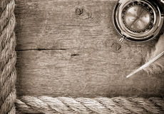 Ship ropes and compass  on old wood. Ship ropes and compass with feather on old wooden background Stock Photos