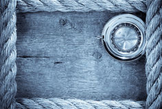 Ship ropes and compass with pen on old vintage. Wooden background Royalty Free Stock Image