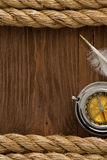 Ship ropes and compass at wood. Ship ropes and compass with feather at old wooden background Stock Photography