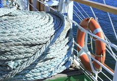 Ship ropes and lifebelt. Reeled coils of a ship ropes at the deck of a sailing ship docked in port Varna Bulgaria Stock Photos
