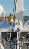 The ship`s bell on the bow with elements of the rigging of the ship on a Sunny day vertically. The ship`s bell on the bow with elements of the rigging of the Stock Image