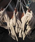 Ship's coiled lines. All running rigging, halyards, lines, rope made fast and/or coiled out of the way for safety and instant deployment aboard ship Stock Photo