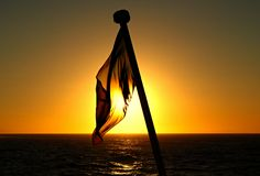 Ship's flag at sunset. royalty free stock photos
