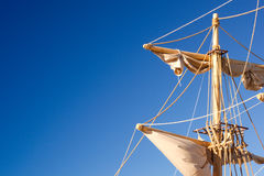 Ship's Mast on Blue. Late afternoon sunlight on a ship's mast with sails and ropes royalty free stock photo