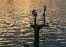 Ship's mast of a small vessel against the sea at sunset Royalty Free Stock Photos