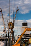Ship's Pulley. Ship's crane pulley against industrial and other ship's masts Stock Photo