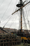 Ship's rigging. Longship moored at Whitby in North Yorkshire UK with lobster pots in foreground Royalty Free Stock Photo