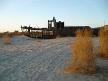 Ship`s skeleton on the bottom of the Aral Sea. Rusty ship on the dried-up bottom of the Aral Sea, which turned into a desert, shows the largest environmental Royalty Free Stock Photos