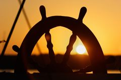 Ship`s wheel on sunset background. Royalty Free Stock Photography