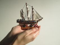 Ship safe in hands. Hands protect a miniature sailing vessel Stock Photography