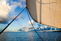 Ship sail, ropes and rainbow over the ocean Stock Photos